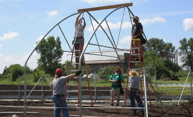 farmworkers putting up a high tunnel